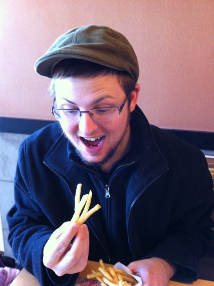 Josh, enjoying some American fries, the type he can no longer get in England.